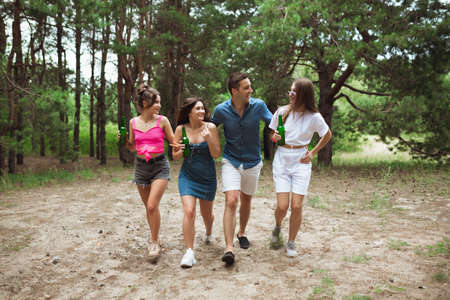 On the way. Group of friends walking down together during picnic in summer forest. Lifestyle, friendship, having fun, weekend and resting concept. Looks cheerful, happy, celebrating, festive.