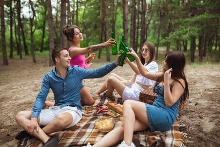 Youth. Group of friends clinking beer bottles during picnic in summer forest. Lifestyle, friendship, having fun, weekend and resting concept. Looks cheerful, happy, celebrating, festive.