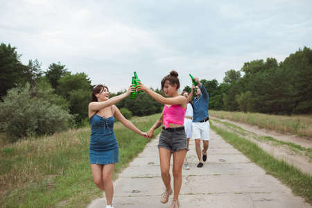 On the way. Group of friends clinking beer bottles during picnic in summer forest. Lifestyle, friendship, having fun, weekend and resting concept. Looks cheerful, happy, celebrating, festive.