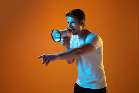 Calling, shouting with megaphone. Caucasian young mans portrait on gradient orange background in neon light. Beautiful male model. Concept of human emotions, facial expression, sales, ad. Copyspace.
