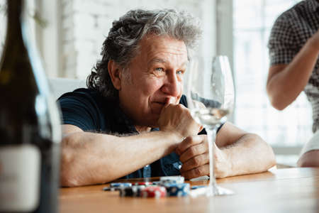 Exciting. Happy mature man playing cards and drinking wine with friends. Looks delighted, excited. Caucasian man gambling at home. Sincere emotions, wellbeing, facial expression concept. Good old age. Stock Photo