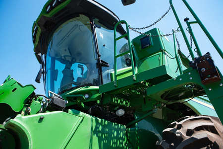 Professional modern tractor, combine at a field in sunlight at work. Vibrant, bright summer colors. Agriculture, exhibition, machinery, plant production. Modern machines at work process.