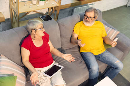 Talking. Couple of seniors spending time together being quarantined - caucasians mature and retired man and woman using modern gadgets, talking, drinking tea. Eyes tired of gadgets life. Lifestyle. Stockfoto