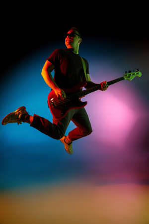 Jumping high. Young inspired and expressive musician, guitarist performing on gradient colored background in neon. Concept of music, hobby, festival, art. Joyful artist, colorful, bright portrait.