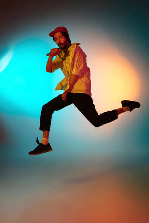 Jumping high. Young inspired and expressive musician, singer performing on gradient colored background in neon light. Concept of music, hobby, festival, art. Joyful artist, colorful, bright portrait. Stok Fotoğraf