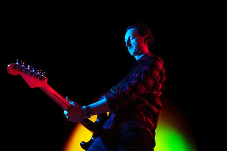 Dark mood. Young inspired and expressive musician, guitarist performing on gradient colored background in neon light. Concept of music, hobby, festival, art. Joyful artist, colorful, bright portrait. Stok Fotoğraf