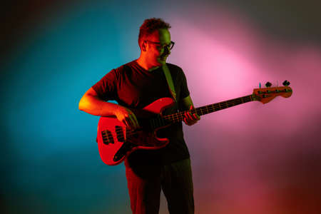 Mood. Young inspired and expressive musician, guitarist performing on gradient colored background in neon light. Concept of music, hobby, festival, art. Joyful artist, colorful, bright portrait.