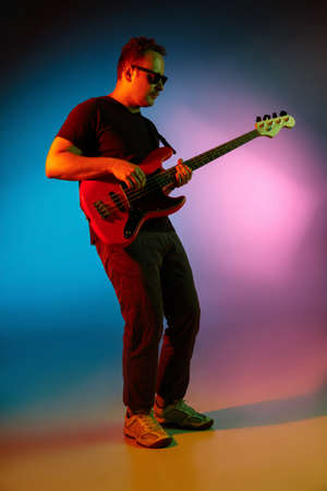 Vibrant. Young inspired and expressive musician, guitarist performing on gradient colored background in neon light. Concept of music, hobby, festival, art. Joyful artist, colorful, bright portrait.
