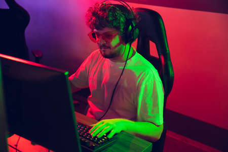 Cyber sport. Fully concentrated professional cybersport gamer playing important match. Caucasian male model practicing, training before tournament alone in neon light. E-sport, gamer, streamer. Reklamní fotografie