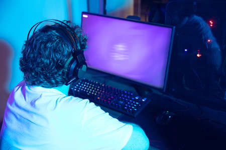 Cyber sport. Copyspace on monitor, screen. Fully concentrated professional gamer playing important match. Caucasian man practicing before tournament alone in neon light. E-sport, gamer, streamer. Reklamní fotografie