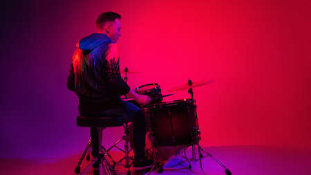 Young caucasian inspired and expressive musician, drummer performing on gradient colored background in neon light. Concept of music, hobby, festival, art. Joyful artist, colorful, bright portrait.