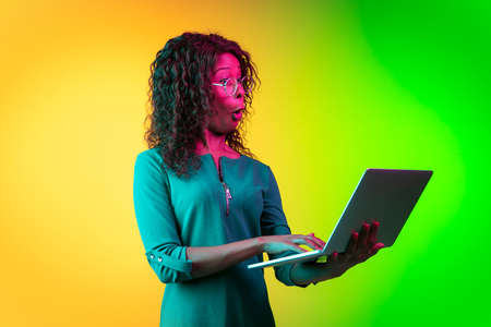 Interested typing on laptop. African-american young woman's portrait on gradient background in neon. Beautiful female model. Concept of cinema, emotions, facial expression, sales, ad. Copyspace. 写真素材