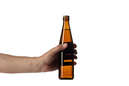 Empty golden colored beer bottle in male hand isolated on white studio background. Concept of beer, beverage, entertainment and alcohol. Copyspace for your bar, restaurant, brewery or shop advertising.