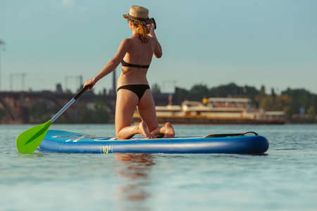 Young attractive woman sitting on paddle board, SUP. Active life, sport, leisure activity concept. Caucasian woman on travel board in summers evening time. Vacation, resort, enjoyment. Cropped. Stock Photo