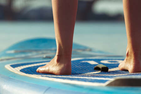 Close up legs. Young attractive woman standing on paddle board, SUP. Active life, sport, leisure activity concept. Caucasian woman on travel board in summers evening time. Vacation, resort, enjoyment.