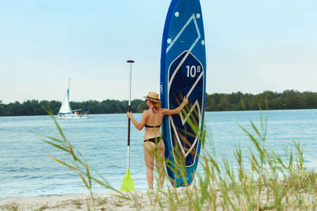 Young attractive woman standing next to paddle board, SUP. Active life, sport, leisure activity concept. Caucasian woman on travel board in summers evening time. Vacation, resort, enjoyment.