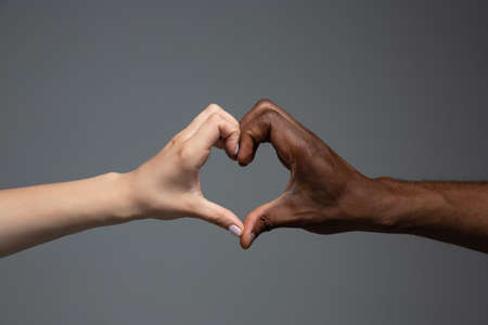 Love heart gesture. Racial tolerance. Respect social unity. African and caucasian hands gesturing on gray studio background. Human rights, friendship, intenational unity concept. Interracial unity. Imagens