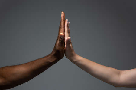 Clapping, teamwork. Racial tolerance. Respect social unity. African and caucasian hands gesturing on gray studio background. Human rights, friendship, intenational unity concept. Interracial unity.