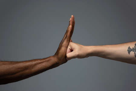Stop racism. Racial tolerance. Respect social unity. African and caucasian hands gesturing on gray studio background. Human rights, friendship, intenational unity concept. Interracial unity.