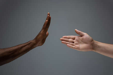 Stop accusation. Racial tolerance. Respect social unity. African and caucasian hands gesturing on gray studio background. Human rights, friendship, intenational unity concept. Interracial unity.