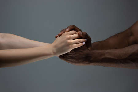 Supporting hands. Racial tolerance. Respect social unity. African and caucasian hands gesturing on gray studio background. Human rights, friendship, intenational unity concept. Interracial unity.