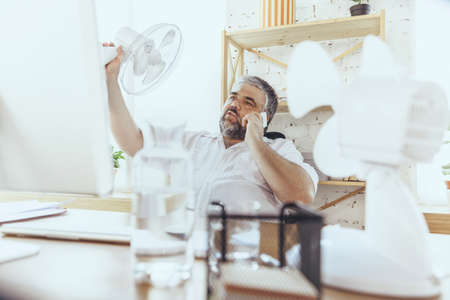 Extremely. Businessman, manager in office with computer and fan cooling off, feeling hot, flushed. Using fan but still suffering of uncomfortable climate in cabinet. Summer, office working, business.