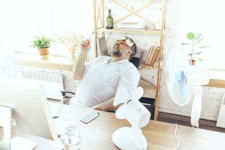 Cant concentrate. Businessman, manager in office with computer and fan cooling off, feeling hot. Using fan but still suffering of uncomfortable climate in cabinet. Summer, office working, business.