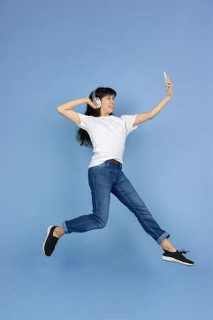 Jumping high, taking selfie with headphones. Portrait of young asian woman isolated on blue background. Beautiful cute girl. Human emotions, facial expression, sales, ad, online shopping concept.