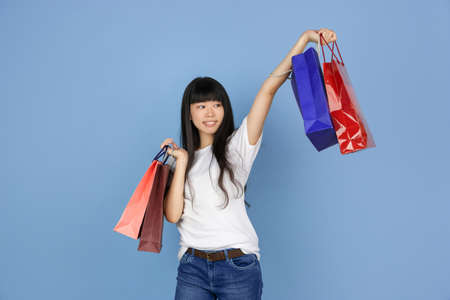 Posing with shopping bags. Portrait of young asian woman on blue studio background. Stylish, trendy. Beautiful and emotional cute girl. Human emotions, facial expression, sales, ad, shopping concept.