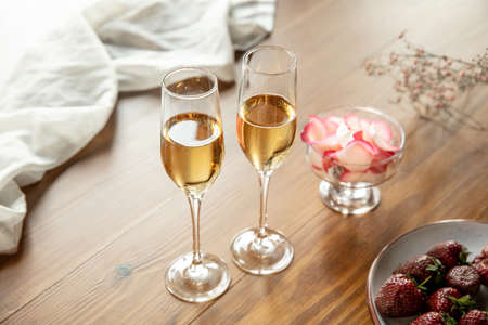 Glasses of sparkling champagne with sweets, close up. Warm colored. Celebration event, holidays, drinks concept. Companion for best family or friend's memories. Anniversary, wedding day or Christmas time.