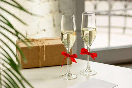 Glasses of sparkling champagne with bows, close up. Warm colored. Celebration event, holidays, drinks concept. Companion for best family or friend's memories. Anniversary, wedding day or Christmas time.