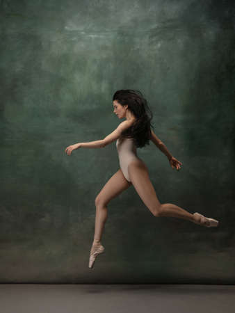 Coming on. Graceful classic ballerina dancing on dark studio background. Pastel bodysuit. The grace, artist, movement, action and motion concept. Looks weightless, flexible. Fashion, style.