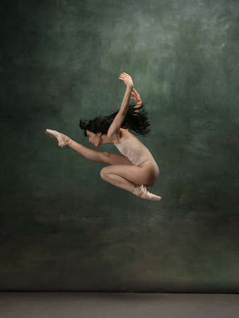Target, achievement. Graceful classic ballerina dancing on dark studio background. Pastel bodysuit. The grace, artist, movement, action and motion concept. Looks weightless, flexible. Fashion, style.