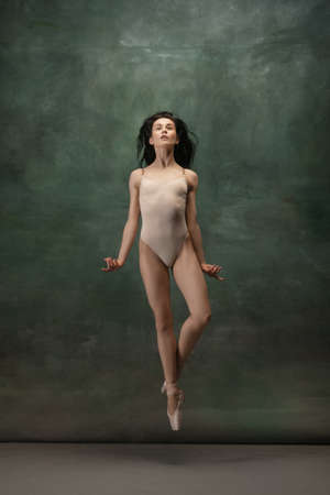 Growth. Graceful classic ballerina dancing on dark studio background. Pastel bodysuit. The grace, artist, movement, action and motion concept. Looks weightless, flexible. Fashion, style.