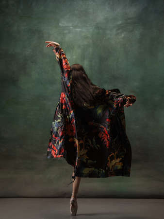 Fashionable. Graceful classic ballerina dancing on dark studio background. Bright coat. The grace, artist, movement, action and motion concept. Looks weightless, flexible. Fashion, style.