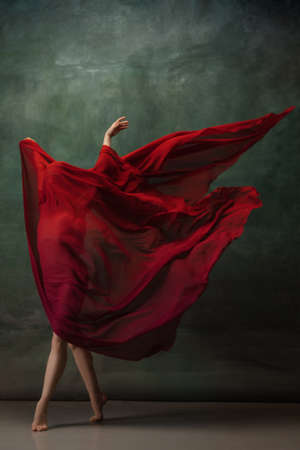 Character. Graceful classic ballerina dancing on dark studio background. Deep red cloth. The grace, artist, movement, action and motion concept. Looks weightless, flexible. Fashion, style.