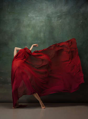 Passioned in motion. Graceful classic ballerina dancing on dark studio background. Deep red cloth. The grace, artist, movement, action and motion concept. Looks weightless, flexible. Fashion, style. 免版税图像