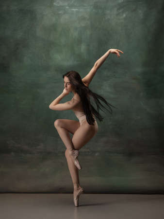 Artwork. Graceful classic ballerina dancing on dark studio background. Pastel bodysuit. The grace, artist, movement, action and motion concept. Looks weightless, flexible. Fashion, style.