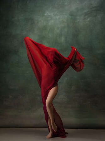Wings flying. Graceful classic ballerina dancing on dark studio background. Deep red cloth. The grace, artist, movement, action and motion concept. Looks weightless, flexible. Fashion, style.