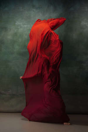 Love emotion. Graceful classic ballerina dancing on dark studio background. Deep red cloth. The grace, artist, movement, action and motion concept. Looks weightless, flexible. Fashion, style.