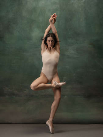 Inspiration. Graceful classic ballerina dancing on dark studio background. Pastel bodysuit. The grace, artist, movement, action and motion concept. Looks weightless, flexible. Fashion, style.