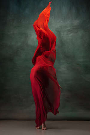 Fire flame. Graceful classic ballerina dancing on dark studio background. Deep red cloth. The grace, artist, movement, action and motion concept. Looks weightless, flexible. Fashion, style. 免版税图像