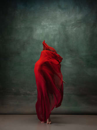 Heart beating. Graceful classic ballerina dancing on dark studio background. Deep red cloth. The grace, artist, movement, action and motion concept. Looks weightless, flexible. Fashion, style.