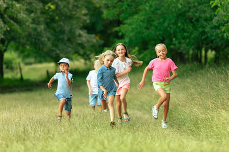 Kids, children running on meadow in summers sunlight. Look happy, cheerful with sincere bright emotions. Cute caucasian boys and girls. Concept of childhood, happiness, movement, family and summer.