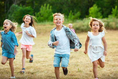 Kids, children running on meadow in summers sunlight. Look happy, cheerful with sincere bright emotions. Cute caucasian boys and girls. Concept of childhood, happiness, movement, family and summer. Banco de Imagens