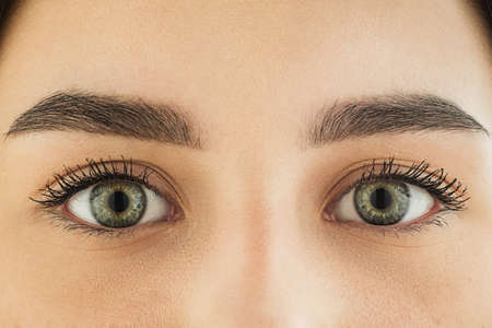 Close up of face, eyes of beautiful caucasian young woman, clear look. Human emotions, facial expression, cosmetology, body and skin care concept. Hopeful, dreamful look, sight. Psychology, fashion. Imagens