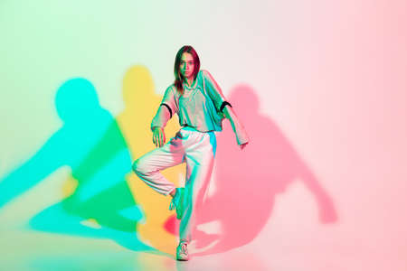 Young beautiful woman dancing hip-hop, street style isolated on studio background in colorful neon light. Fashion and motion, youth, music, action concept. Trendy clothes. Copyspace for ad. 免版税图像