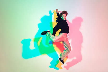 Young beautiful man dancing hip-hop, street style isolated on studio background in colorful neon light. Fashion and motion, youth, music, action concept. Trendy clothes. Copyspace for ad.