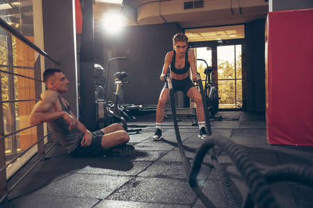 Beautiful young sporty couple workout in gym together. Caucasian man training with female trainer. Concept of sport, activity, healthy lifestyle, strength and power. Working out with ropes. 版權商用圖片