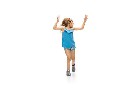 Happy kids, little and emotional caucasian girl jumping and running isolated on white background. Look happy, cheerful, sincere. Copyspace for ad. Childhood, education, happiness concept.
